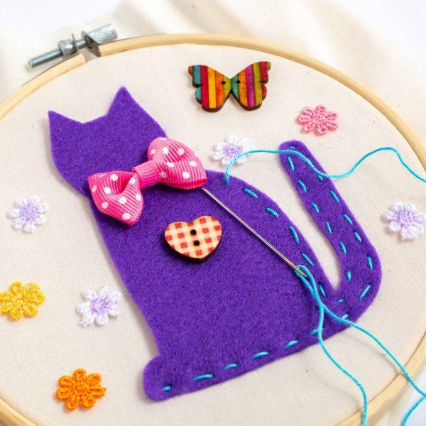 חישוק רקמה מעץ עם ציור של חתול סגול עם פפיון