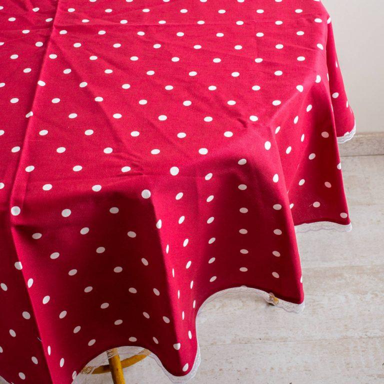 נקודות לבנות עם רקע אדום מצוירות על גבי מפת שולחן עגולה